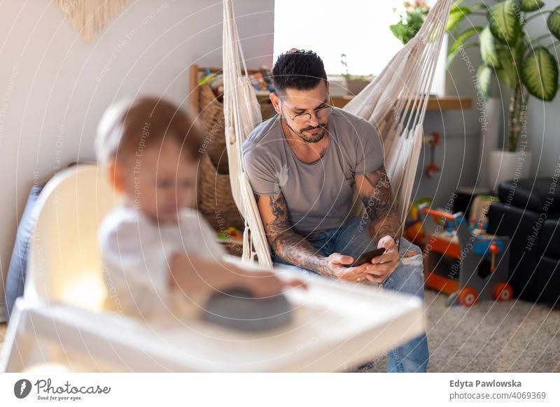 Bleiben Sie zu Hause Vater auf Smartphone ignorieren Kind alleinerziehend alleinerziehender Vater Vatertag Vaterschaft zu Hause bleiben Dad Vaterschaftsurlaub