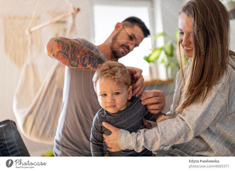 Junges Paar kleidet ihren kleinen Sohn zu Hause Familie Vater Kind Mädchen bezaubernd Kleinkind Kindererziehung Raum Tochter Appartement gutaussehend Spielen