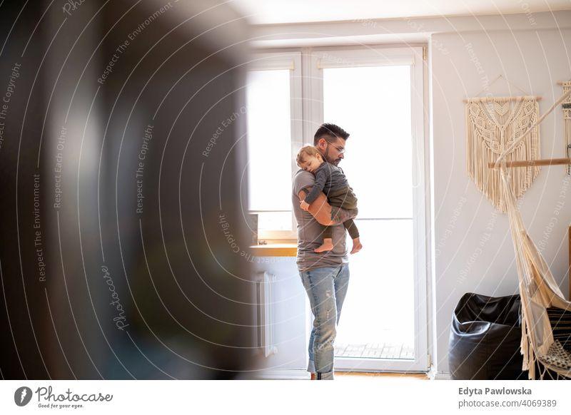 Papa legt Baby in seinen Armen zu Hause schlafen alleinerziehend alleinerziehender Vater Vatertag Vaterschaft zu Hause bleiben Dad Vaterschaftsurlaub