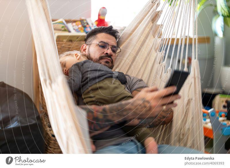 Mann überprüft sein Telefon, während sein kleiner Babysohn schläft alleinerziehend alleinerziehender Vater Vatertag Vaterschaft zu Hause bleiben Dad