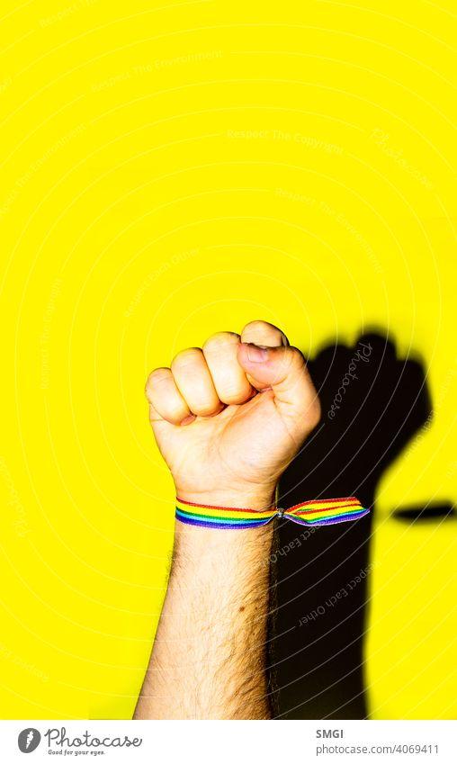 Die hochgehaltene Faust eines Mannes mit einem Armband in den Farben der schwulen Flagge. feiern Feier farbenfroh Gemeinschaft Diskriminierung Vielfalt gleich