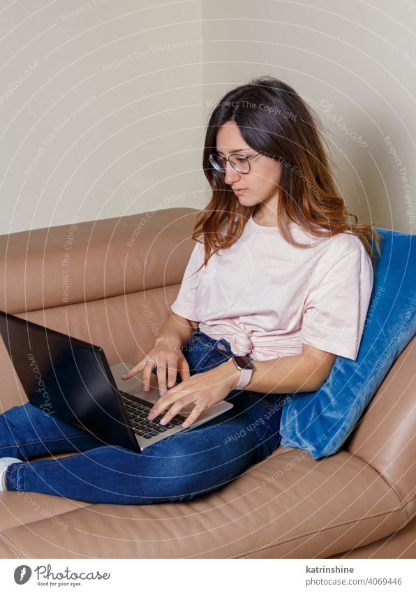 Junge Frauen verwenden einen Laptop, während sie zu Hause auf dem Sofa sitzen jung anhaben Attrappe T-Shirt lernen Schüler Lifestyle Jeanshose Brille ernst