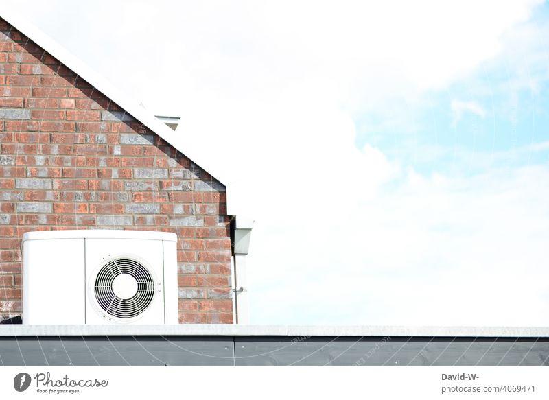 weiße Wärmepumpe an einem Haus Luftwärmepumpe Luftwasserwärmepumpe Energiewirtschaft Energiegewinnung nachhaltig ökologisch Luft-Wasser-Wärmepumpe innovativ