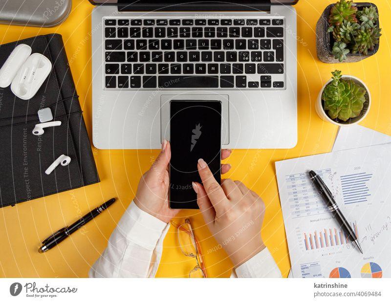 Business Frau Hände mit Smartphone Ansicht von oben verwenden Dokumente Handy-Berichte gelb Laptop Schreibtisch Büro Draufsicht Kaffee Kaukasier gesichtslos