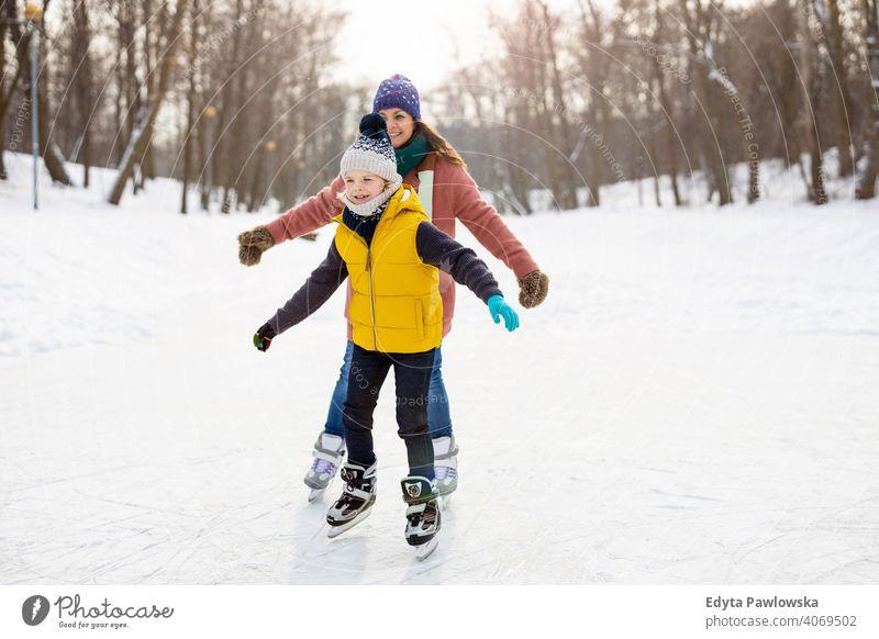 Mutter und Sohn beim Schlittschuhlaufen auf gefrorenem Teich Tochter Saison Zusammensein heiter Spaß Kind Menschen Park Feiertag Wald Kindheit Frau Mädchen