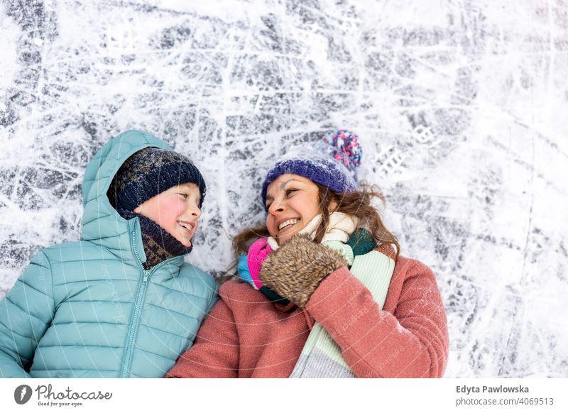 Mutter und Sohn liegend auf gefrorenen See Oberfläche und lächelnd Tochter Saison Zusammensein heiter Spaß Kind Menschen Park Feiertag Wald Kindheit Frau
