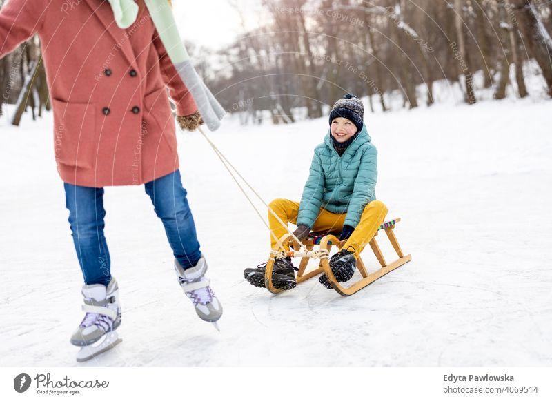Mutter und Sohn haben einen großen Wintertag im Freien spielen im Schnee Tochter Saison Zusammensein gefroren heiter Spaß Kind Menschen Park Feiertag Wald