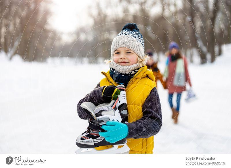 Kleiner Junge geht Schlittschuhlaufen mit seiner Familie Mutter Sohn Tochter Saison Zusammensein gefroren heiter Spaß Kind Menschen Park Feiertag Wald Kindheit
