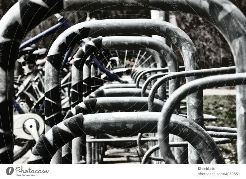 Schwarz-Weiß-Aufnahme  Zentraler Blick durch einen Fahrradständer Rad parken schwarz weiß schwarz-weiß Metall Speichen Fahrradfahren Detailaufnahme Straße