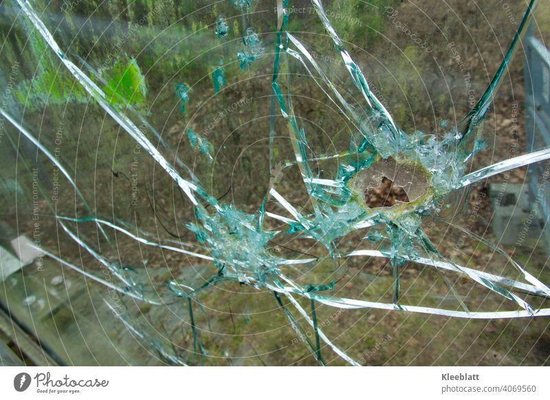 Zerbrochene Panzerglasscheibe einer Fußgängerbrücke - Detailaufnahme Zerbrochenes Fenster panzerglas Loch Splitter Glas kaputt Zerstörung Farbfoto Außenaufnahme