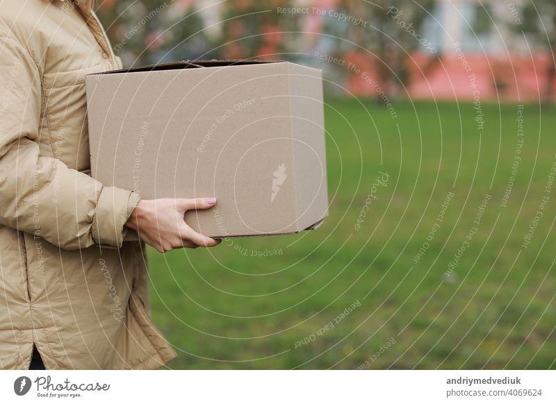 Cropped Delivery Mädchen halten leeren Karton im Freien auf einer Wohnanlage Hintergrund. Service Koronavirus. Online-Shopping. mock up. Kasten Coronavirus