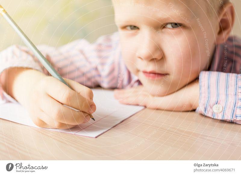 Süßer Junge schreibt seine Hausaufgaben und schaut in die Kamera. Kind lernen schreibend Tun niedlich konzentriert blond rosa Hemd Bleistift Schönschreibheft