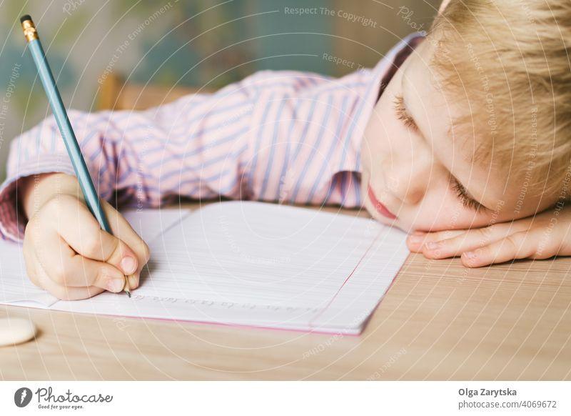 Kind schreibt in ein Notizbuch und liegt auf dem Schreibtisch. Junge lernen schreibend wenig müde schlafen Tun niedlich blond rosa Hemd Bleistift