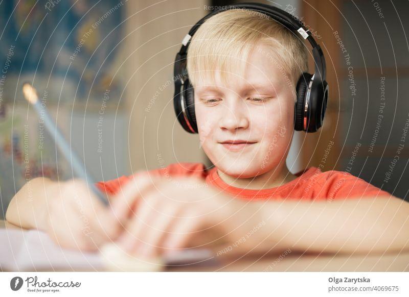 Junge mit Kopfhörer schreibt und lächelt. Lächeln schreibend Kind im Innenbereich niedlich Hausaufgabe Spaß Kaukasier blond Hand Bleistift Behaarung Gesicht