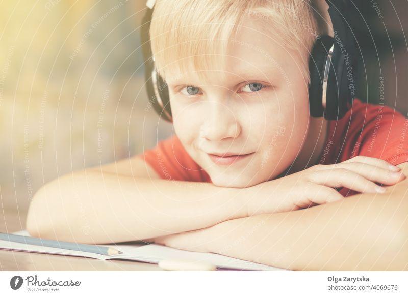 Blondy Teenager-Junge in Kopfhörer ruht und Musik hören . Lächeln Kind im Innenbereich niedlich grau Auge Hausaufgabe Spaß Kaukasier blond Hand Bleistift