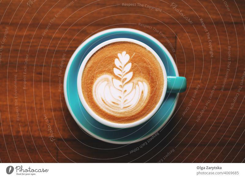 Eine Tasse Cappuccino mit Latte Art auf Holztisch. Kunst schäumen macchiato Top Ansicht Hintergrund Design Sahne Muster Kaffee Aroma Frühstück braun Café