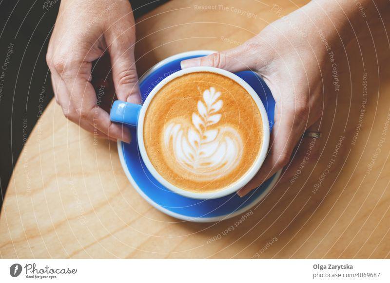 Die Hand einer Frau hält einen Kaffee mit Latte Art. Kunst Cappuccino Tasse Becher Hintergrund Person altehrwürdig weiß Café trinken Espresso heiß Top Getränk