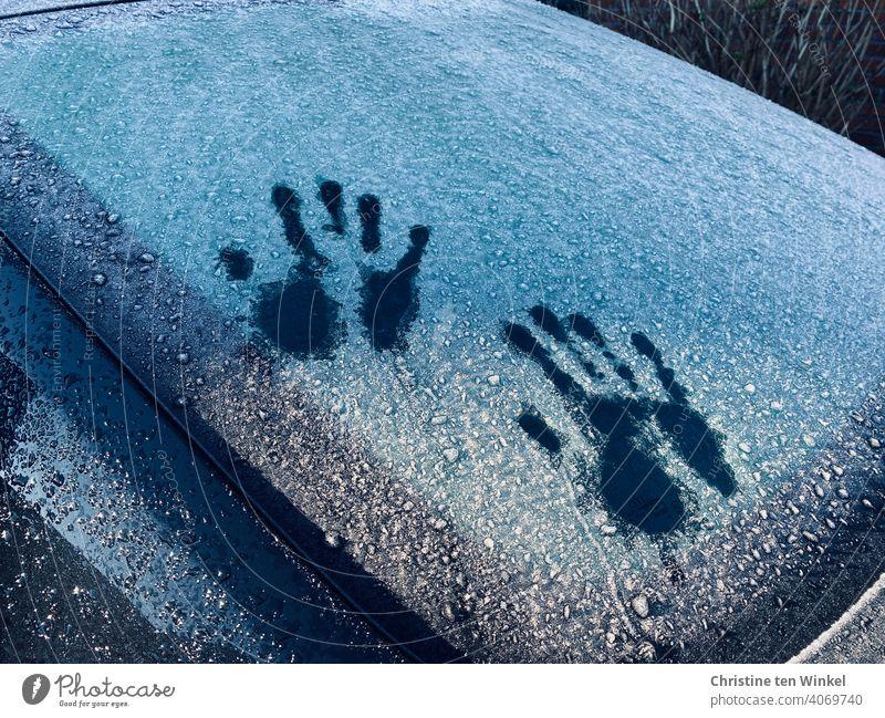 Zwei Handabdrücke auf einer gefrorenen Auto Heckscheibe, teils von der Sonne beschienen Scheibe Glas Umrisse Handabdruck Autoscheibe Frontscheibe Eis vereist