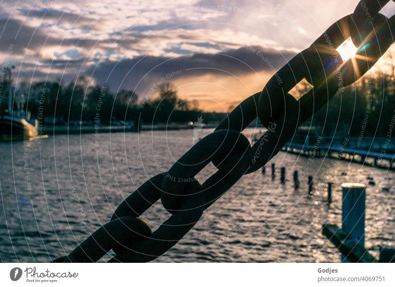 Sonne scheint durch das Glied einer massiven Stahlkette gegen den bewölkten Himmel der Abenddämmerung über dem Fluss anketten Kettenglieder Sonnenstrahlen