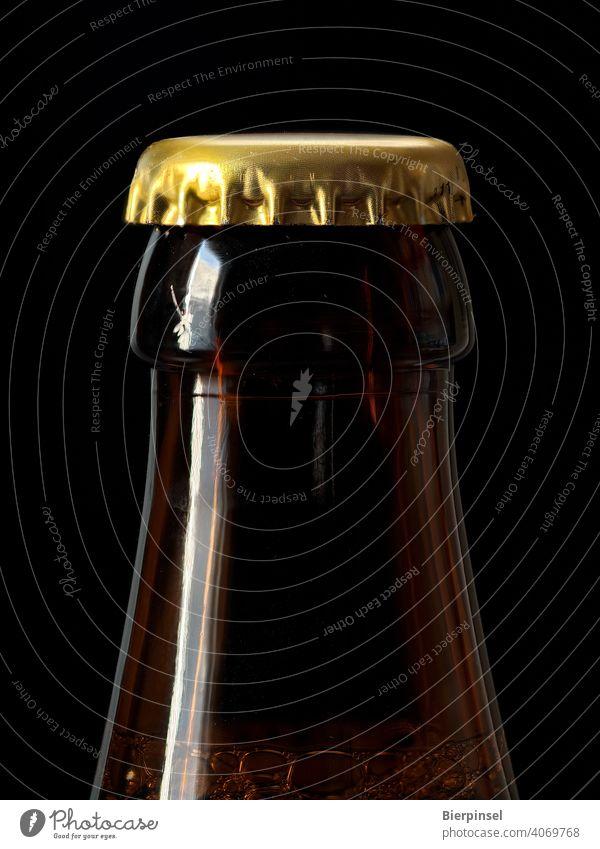 Mit einem Kronenkorken verschlossene Bierflasche Kronkorken Flasche Verschluss Zacken Blech Glas golden braun Getränk trinken Großaufnahme ungeöffnet luftdicht