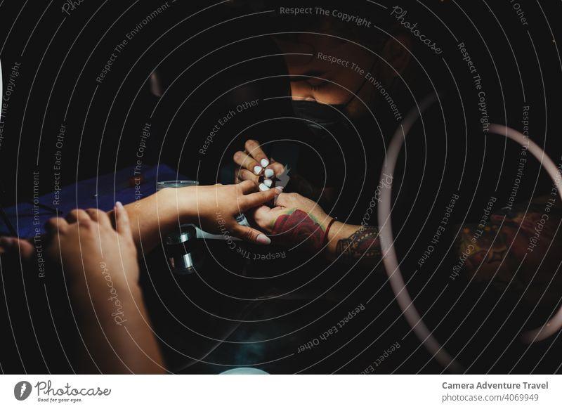 Maniküre Mann trägt Harz auf die Nägel einer Kundin auf, Nahaufnahme Pflege nageln Kissen erfahren Finger Hand Job berühren Gefühl achtsam Frau Salon Mode