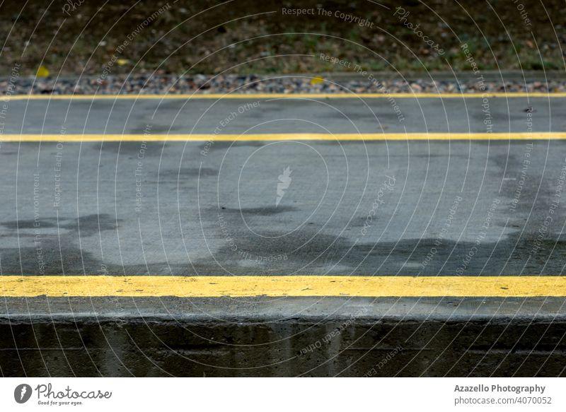 Gelbe Linien und Pfeile auf einem nassen Betonweg im Park. Asphalt Hintergrund schwarz Großstadt dunkel Tag Regie Laufwerk grau Anleitung Autobahn zeigen Reise