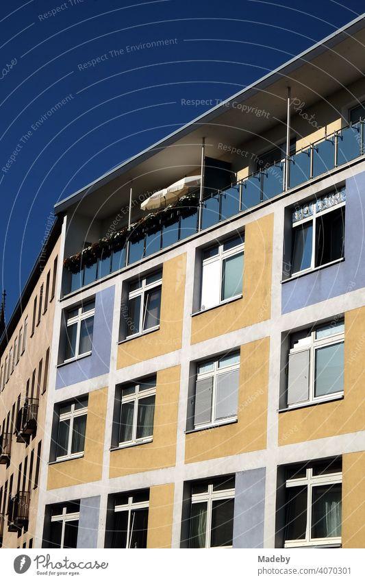 Restaurierte zweifarbige Fassade in Beige und Blau mit überdachtem Balkon im Sommer bei Sonnenschein in der Innenstadt von Frankfurt am Main in Hessen Wohnhaus