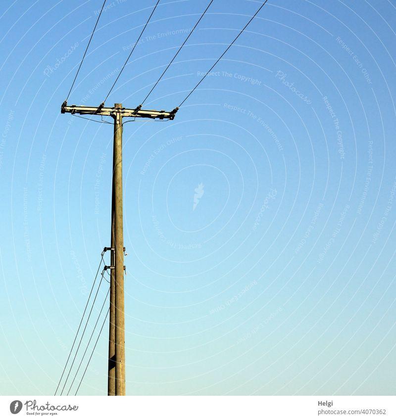 Strommast aus Holz mit Stromleitungen alt Kabel Elektrizität Leitung Energiewirtschaft stromleitung Stromtransport Außenaufnahme CO2 Himmel blauer Himmel