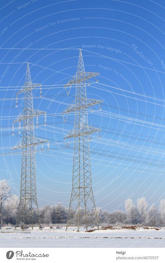 riesige Strommasten mit Raureif bedeckt in winterlicher Landschaft mit blauem Himmel zwei Hochspannungsmast Stromversorgung Energieversorgung CO2 Elektrizität