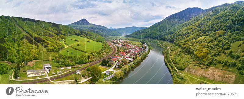 Dorf, Fluss und Straße in Bergtal. Grüne Bergwiesen und Hügel. Kraľoviansky Mäander auf Fluss Bar. Frühling-Panorama Berge u. Gebirge Tatra Wiese Landschaft
