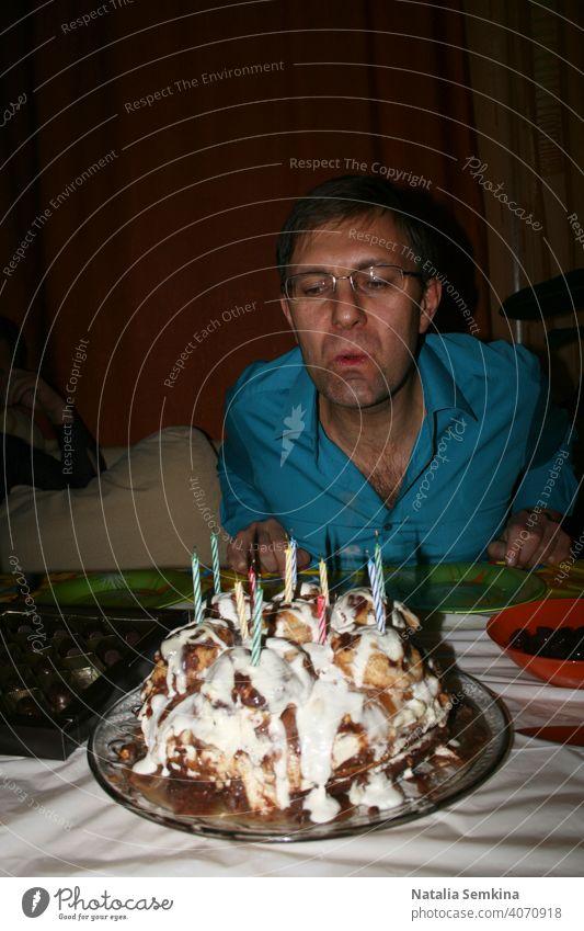 Mann in blauem Hemd Ausblasen brennenden Kerzen auf handgemachte festlichen Kuchen in dunklen Raum. Geburtstagsfeier zu Hause. Party zu Hause. Taille Porträt. Vertikale Ausrichtung.