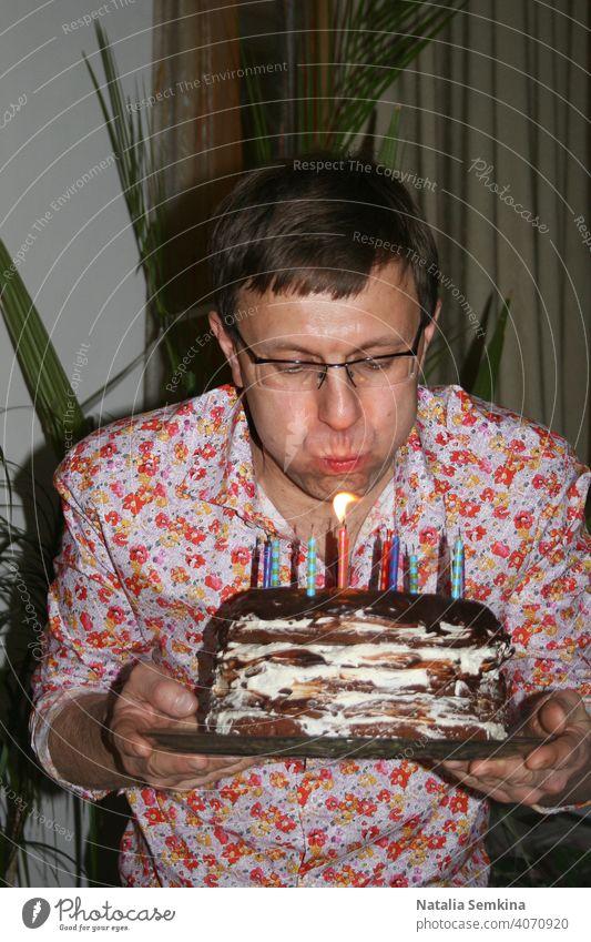 Mann in floralem Hemd hält handgemachten festlichen Kuchen in den Händen und bläst brennende Kerzen im dunklen Raum aus. Geburtstagsfeier zu Hause. Party zu Hause. Taille Porträt. Vertikale Ausrichtung.