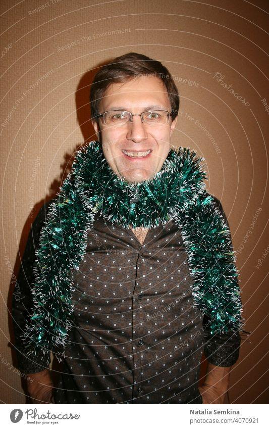 Fröhlich lächelnder Mann mit Brille und braunem Hemd mit grünem Lametta um den Hals, der an einer beigen Wand steht und in die Kamera schaut. Taillenporträt. Weihnachtsfeier zu Hause.