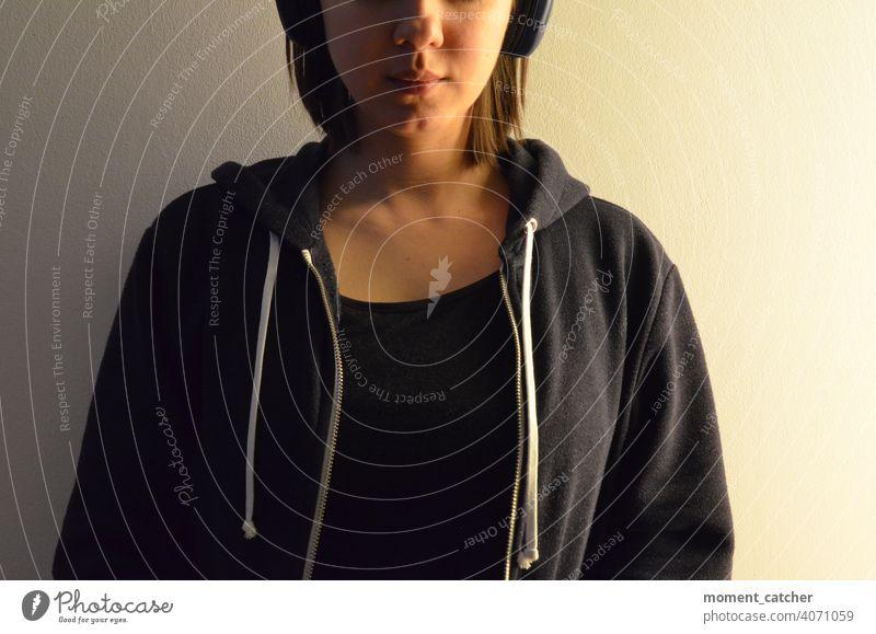 Frau mit Kopfhörern sitzt vor weißer Wand Musik hören Podcast hörbuch Konzentration konzentriert konzentrieren Erholung Freizeit & Hobby entspannung Bluetooth
