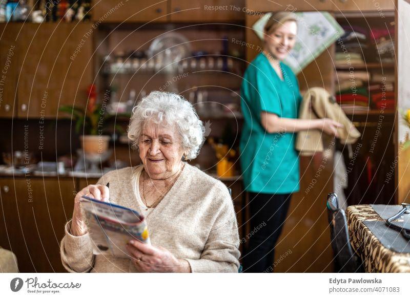 Weibliche Krankenschwester kümmert sich um eine ältere Frau zu Hause echte Menschen offen Senior reif Kaukasier heimwärts alt Alterung häusliches Leben