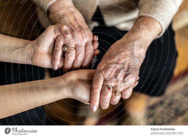 Ausgeschnittene Aufnahme einer älteren Frau, die mit einer Krankenschwester Händchen hält Hände tröstlich Händchenhalten knittern echte Menschen offen Senior