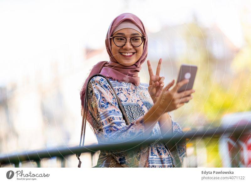 Junge Frau trägt einen Hijab und macht ein Selfie Kopftuch muslimisch Islam arabisch Sommer Mädchen Menschen junger Erwachsener Lifestyle aktiv im Freien