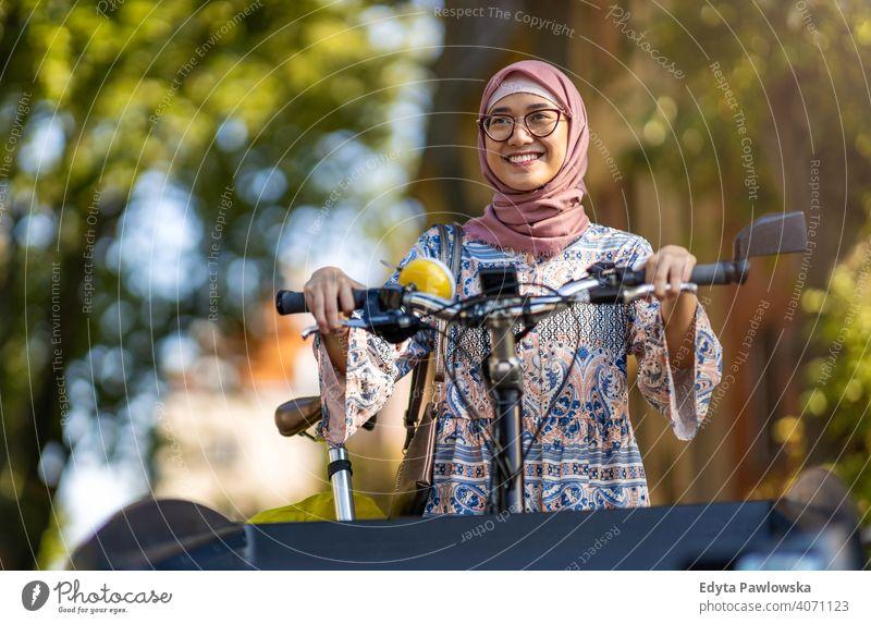 Selbstbewusste muslimische Frau mit Lastenfahrrad im städtischen Bereich Hijab Kopftuch Islam arabisch Sommer Mädchen Menschen junger Erwachsener Lifestyle