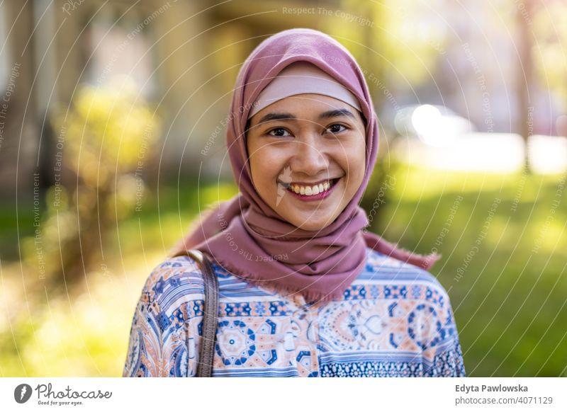 Lächelnde junge Frau trägt Hijab im Freien Kopftuch muslimisch Islam arabisch Sommer Mädchen Menschen junger Erwachsener Lifestyle aktiv tausendjährig außerhalb