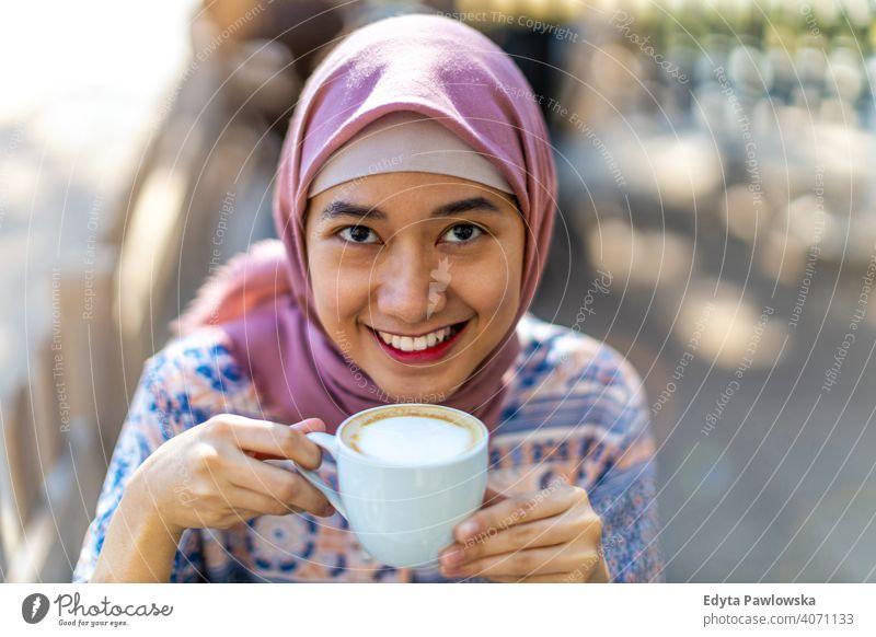 Glückliche junge muslimische Frau trinkt Kaffee Hijab Kopftuch Islam arabisch Sommer Mädchen Menschen junger Erwachsener Lifestyle aktiv im Freien tausendjährig