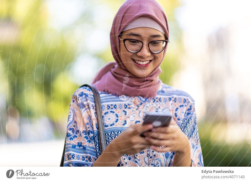 Lächelnde junge muslimische Frau mit Handy im Freien Hijab Kopftuch Islam arabisch Sommer Mädchen Menschen junger Erwachsener Lifestyle aktiv tausendjährig