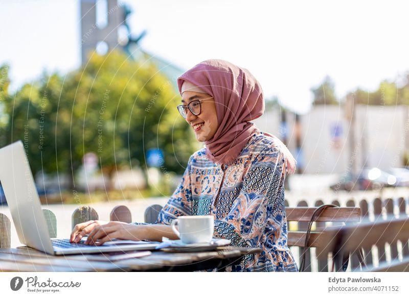 Junge muslimische Frau, die einen Laptop in einem Straßencafé benutzt Hijab Kopftuch Islam arabisch Sommer Mädchen Menschen junger Erwachsener Lifestyle aktiv