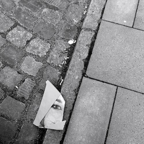 achtlos bild portrait plakat ausriss abschnitt straße pflasterstein Zigarettenstummel frau gesicht auge blick papier gehweg