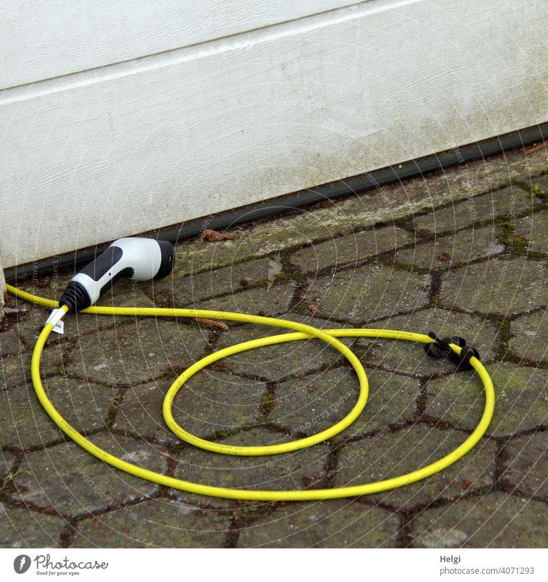 gelbes Ladekabel mit Stecker  liegt vor einer Garage  und wartes auf das Elektroauto Kabel Stromversorgung Elektrizität Technik & Technologie Elektrisches Gerät