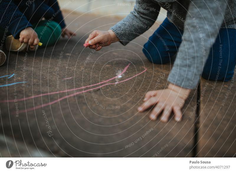 Kind zeichnet mit farbiger Kreide auf dem Boden Kreidezeichnung Kreativität Zeichnung Kindheit Straße Spielen Freude Kinderspiel Kunst Freizeit & Hobby