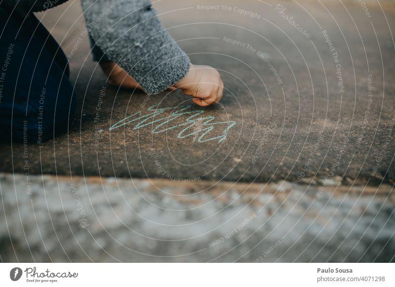 Kind zeichnet mit farbiger Kreide auf dem Boden Kreidezeichnung Kreativität Spielen Zeichnung Kindheit Straße zeichnen Strassenmalerei Freude Asphalt