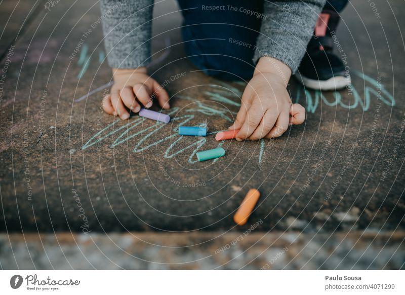 Kind zeichnet mit farbiger Kreide auf dem Boden zeichnen Zeichnung Strassenmalerei Kreidezeichnung Spielen Kindheit Kreativität malen Straße Kunst Kinderspiel