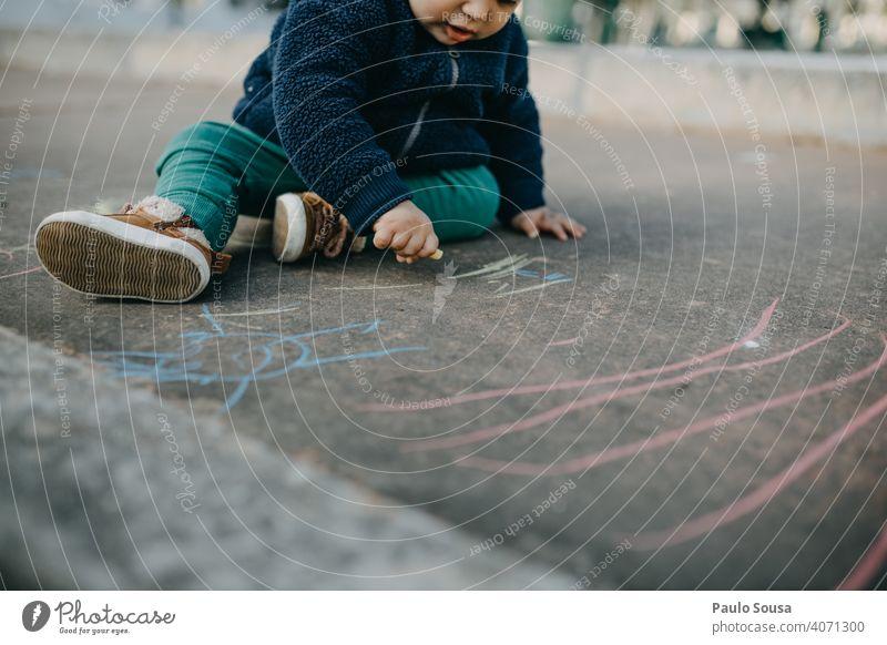 Kind zeichnet mit farbiger Kreide auf dem Boden Kaukasier 1-3 Jahre authentisch Kreidezeichnung Kindheit Spielen Farbfoto Strassenmalerei Kunst malen zeichnen