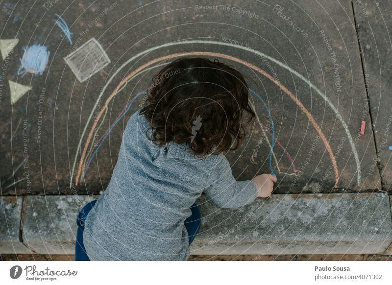 Kind zeichnet mit farbiger Kreide auf dem Boden Kreidezeichnung Kindheit Gemälde Straße Spielen Zeichnung Asphalt zeichnen Strassenmalerei Außenaufnahme