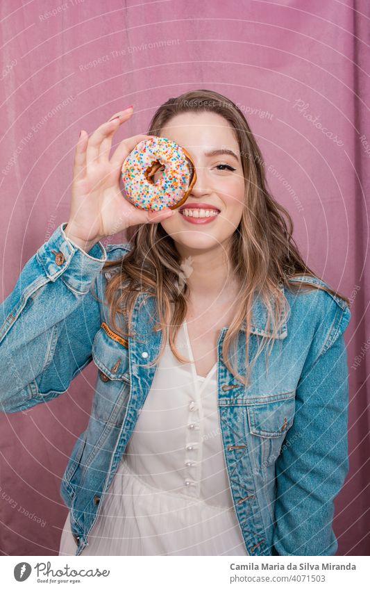 Schöne Frau hält einen Donut. attraktiv Hintergrund Bäckerei schön Schönheit heiter farbenfroh Konditorei niedlich lecker Dessert Krapfen Donuts Doughnut Ostern